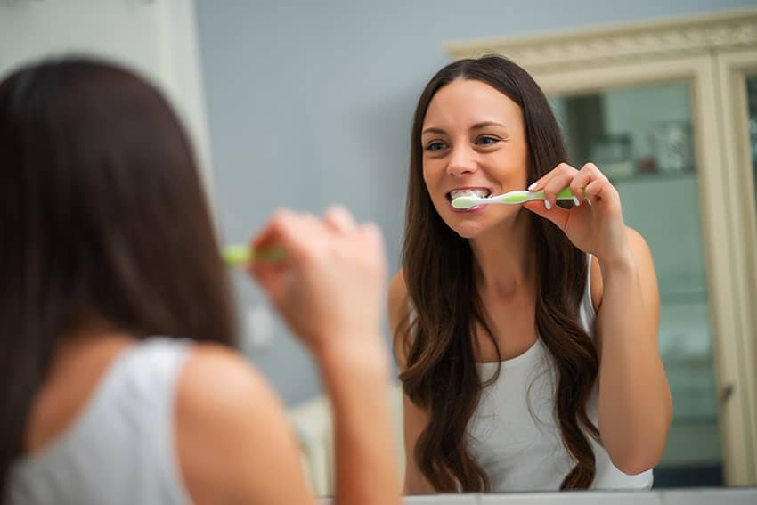 Young woman brushing teeth in front of her bathroom mirror