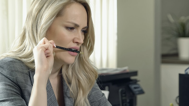 A beautiful woman sits a her desk, chewing on a pen. Chewing on these and other nonfoods is linked to TMJ and migraines.
