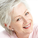 Gray haired woman shows off her smile