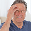 Middle aged man suffers from a headache at home