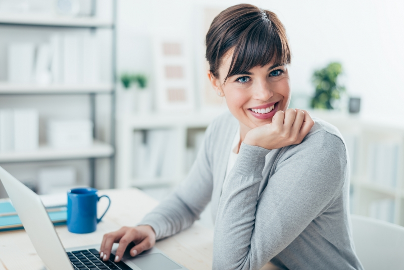 attractive woman works on her laptop at home