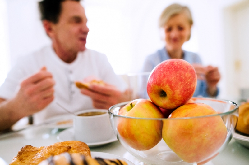 couple enjoying a meal with family, apples in a bowl
