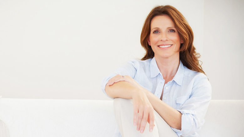 Smiling mature woman sitting on sofa