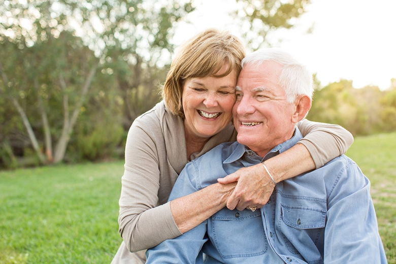 An elderly couple smiling and hugging while outdoors