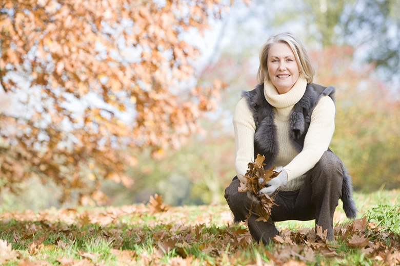 A elderly woman crouching in fall leaves