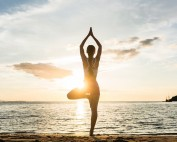 A woman does a yoga pose on the beach, like the one on Hilton Head Island. She understands how yoga helps her focus and challenges her nerves and muscles.