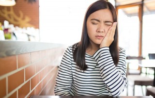 Young asian woman sitting at a table at a diner with a toothache & sensitivity. Maybe you have added more brushing or flossing into your daily routine. Perhaps you changed your toothpaste. No matter what you've done, nothing seems to be helping. At Durham in Hilton Head, we have some expert suggestions that can save you some time and pain.