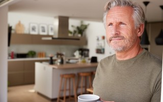 Middle aged man standing in his kitchen looking out the door with his cup of coffee. When we have a headache we often go for a cup of caffeine. Is that coffee actually causing your headaches?