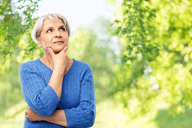 Older woman pondering questions while taking a walk in the park