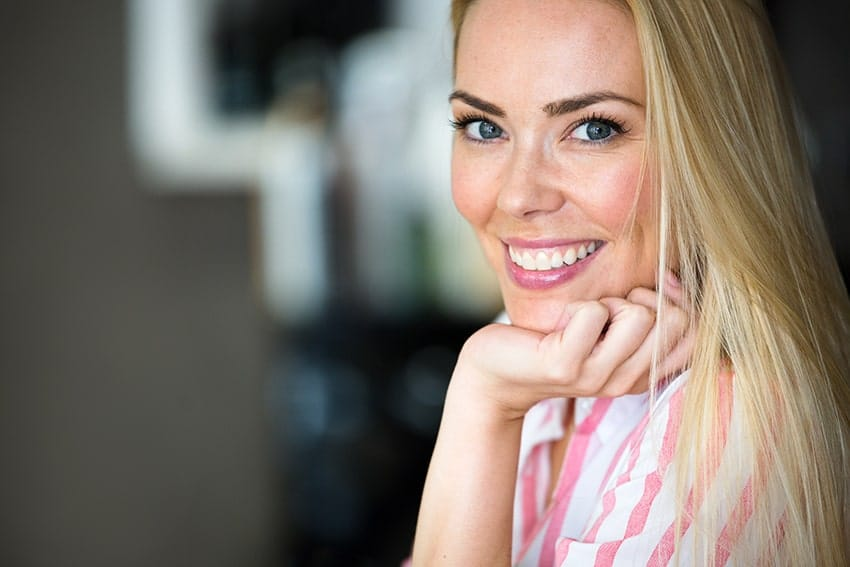 Beautful young blonde woman showing off her smile with Invisalign