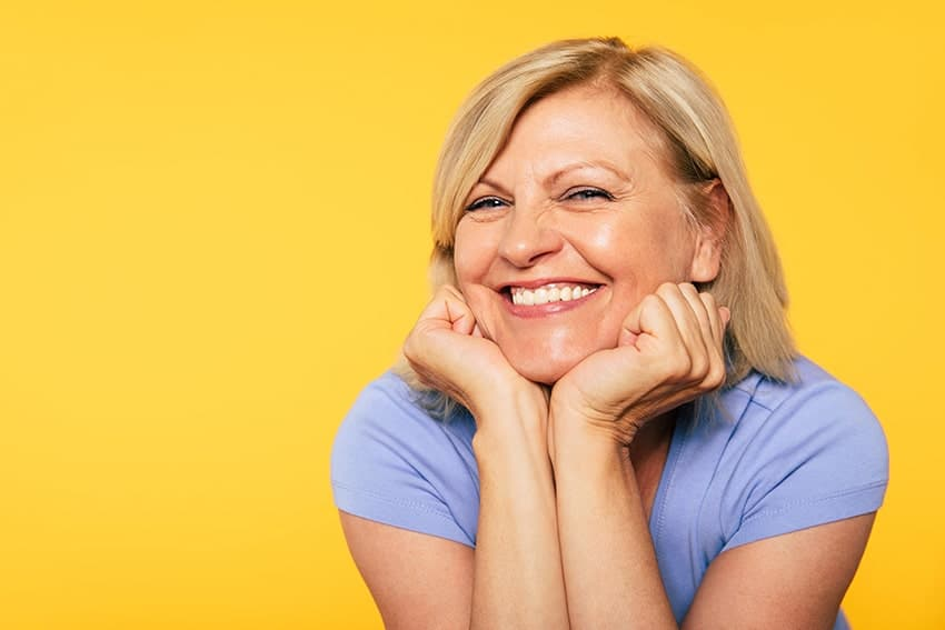 Mature woman stands in front of a yellow background, showing her amazing non-surgical facelift off