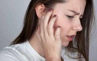 woman with an itchy ear, suffering from TMJ