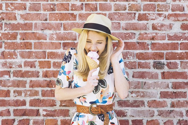 cute young woman in summer hat and dress enjoys an ice cream cone