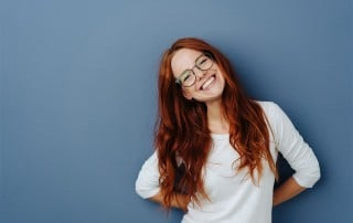 Cute red haired woman tilts her head and shows off her amazing smile